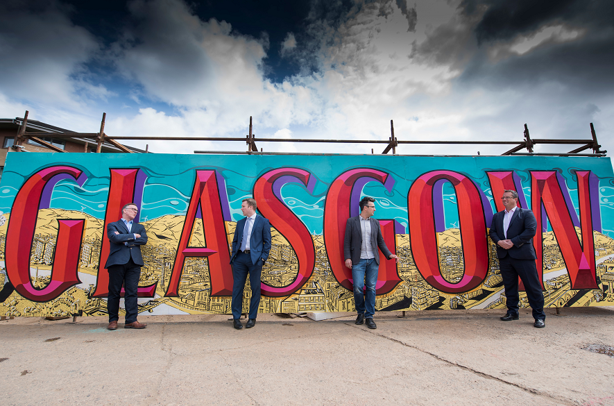 Four men standing in front of giant Glasgow sign
