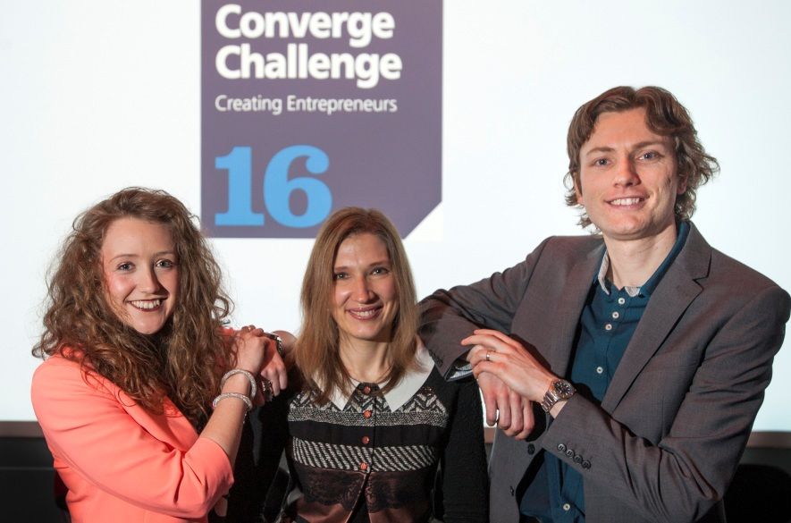 Two women and one man in front of a Converge Challenge sign