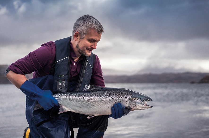 Man holding salmon next to sea