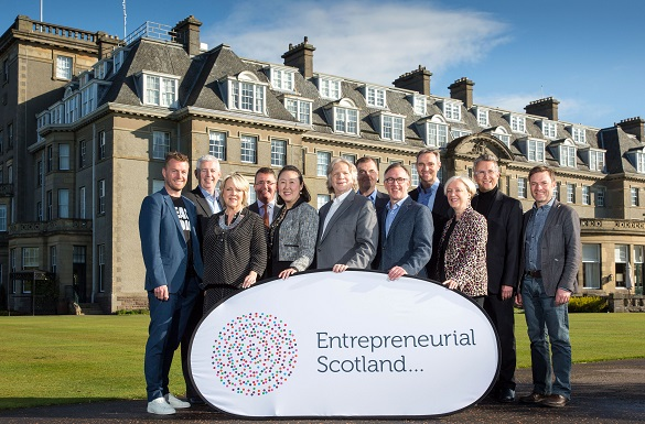 12 people standing outside a hotel with a sign that says Entrepreneurial Scotland