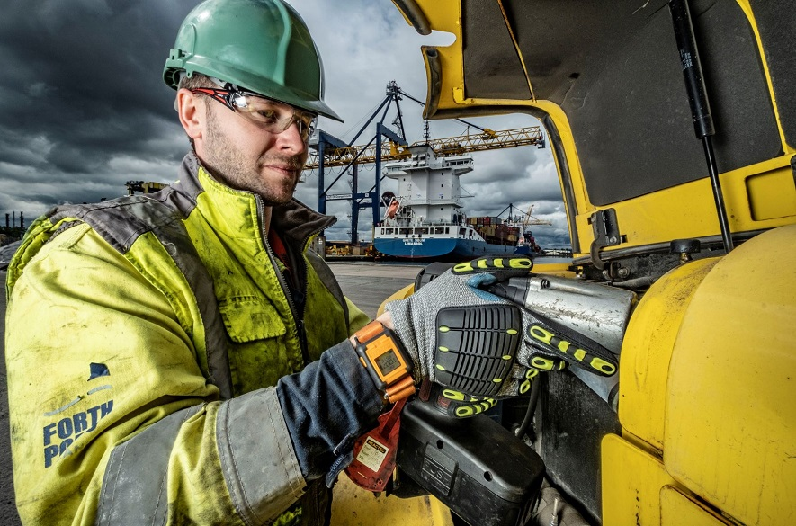Man in safety gear operating a drill at a port